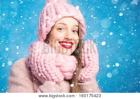 Winter portrait of a beautiful woman in knitted pink scurf, gloves and hat with snow flake on the blue background during the snowfall poster
