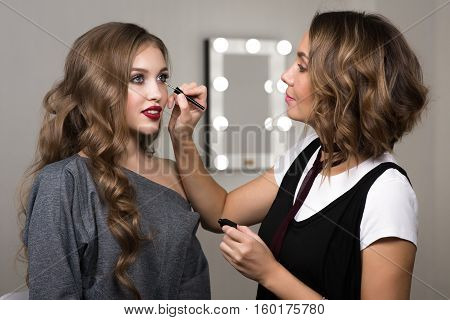 Makeup process, makeup artist colors model at salon. Portrait of two beautiful women