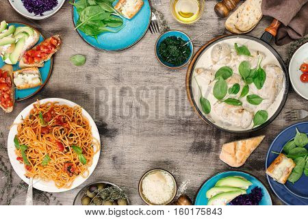 Frame from various food chicken breast in a creamy sauce Italian pasta and appetizers on the wooden table top view