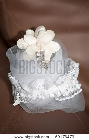 bridal accessories - laced garter silver crystal hanging earrings and veil placed on brown leather sofa