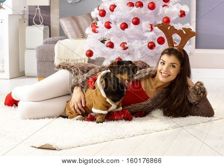 Happy young woman lying on floor by christmas tree, smiling, hugging dog.