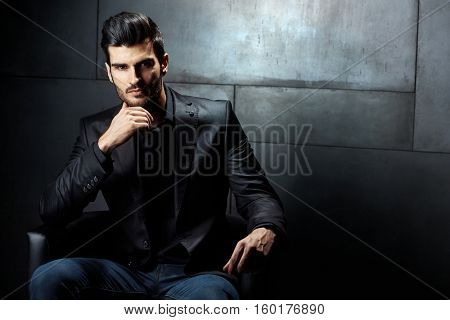 Confident serious businessman sitting in armchair, looking at camera.