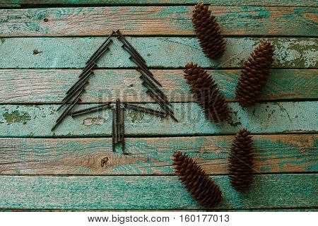 Nails in the form of a Christmas tree on a wooden surface. Joinery tradition. The concept of a New Year's background for building the store.