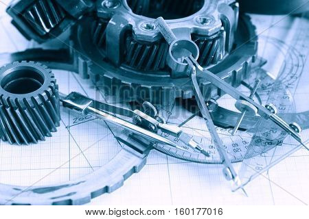 Engineering concept. Set of gears near divider on blueprint