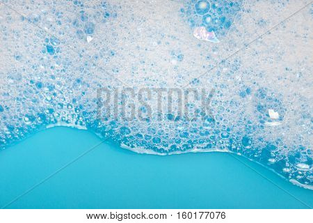 White foam abstract bubbles on blue background.
