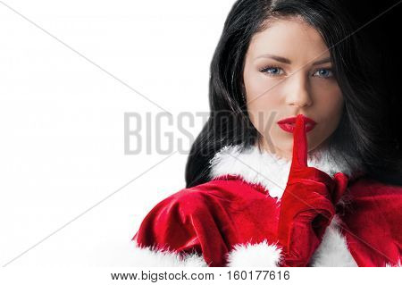 Portrait of beautiful woman in Santa Christmas costume with finger on lips
