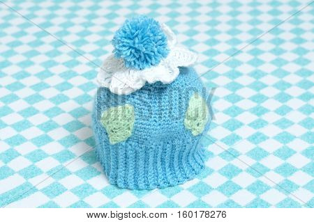 knitted cap for babies decorated with pompon, flowers and leaves