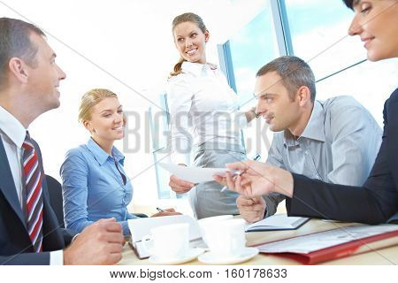 Secretary handing out spreadsheet at in office