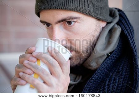 Homeless whit dirty hands drinking alone from a plastic glass