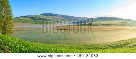 Autumn fog at sunrise over the meadow, Dolomites, Italy