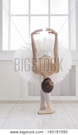 Classical Ballet dancer reverence. Beautiful graceful ballerine practice ballet positions in tutu skirt near large window in white light hall. Ballet class training, high-key soft toning.