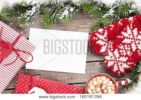 Christmas greeting card, fir tree, mittens, gift boxes and hot chocolate on wooden table. Top view with copy space