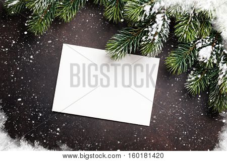 Christmas greeting card and fir tree over stone background. Top view with copy space
