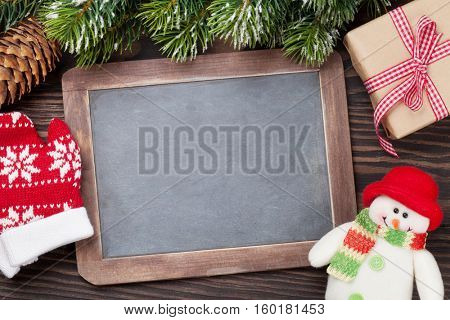 Christmas chalkboard, snowman, gift box, mittens and fir tree. Top view with copy space for your text