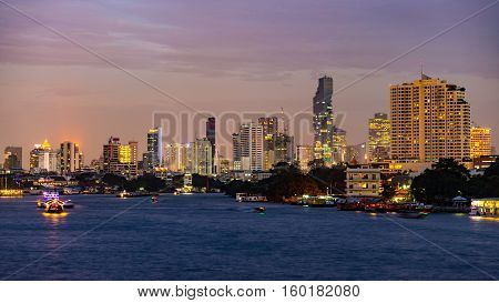 Boats cruising on the Chao Praya River at Bangkok Thailand. Scenic illuminated skyline at dusk in the background.