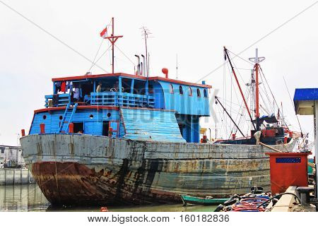 Colorful rusty phinisi ship in harbor with fishermen on board. Sunda Kelapa Harbor Jakarta Indonesia. Blue and red colored rusty old Phinisi ship.
