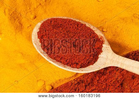 Background of curcuma and chili pepper powder with wooden spoon