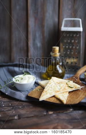 Focaccia with olive oil cheese white sause and herbs. Homemade traditional Italian bread focaccia on the linen napkin.