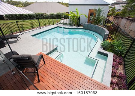 Modern swimming pool rest area view from above with chairs on the wooden floor with a garden including colorful plants which covered with a fence beside a green lawn and houses in residential areas