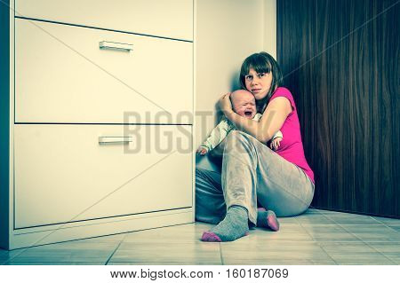 Abusing wife and crying baby covering in the corner at home - domestic violence - retro style
