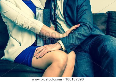 Man touching woman's knee - sexual harassment in business office - retro style