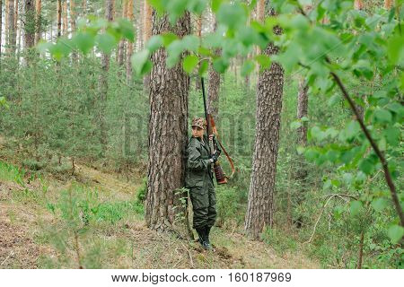 Woman hunter with a gun. Hunting in the woods.