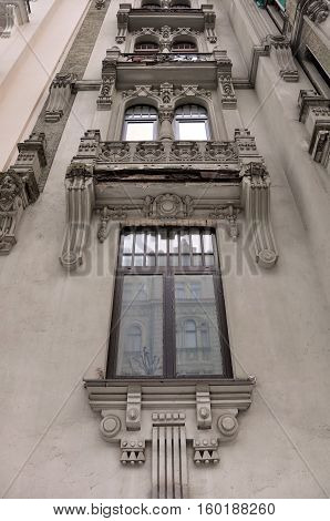 Looking up at the facade of old building with sculptures in Art Nouveau style (Jugendstil). Riga, Latvia.