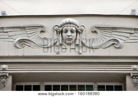 Facade of old building with sculptures of woman heads in Art Nouveau style (Jugendstil). Riga, Latvia.