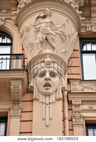 Looking up at the facade of old building with sculpture of woman heads in Art Nouveau style (Jugendstil). Riga, Latvia.
