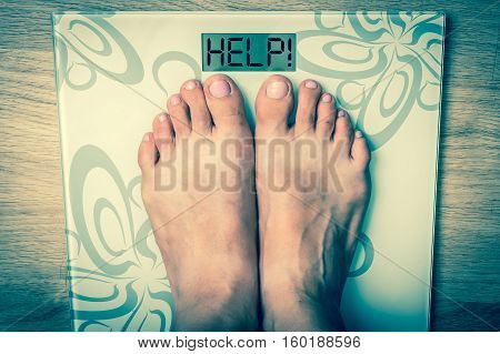 Woman's feet on a scale with word HELP! - obesity concept - retro style