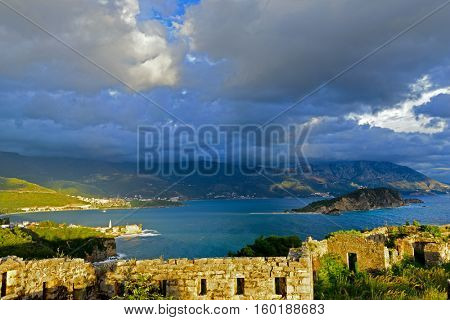 View to Budva Old town and bay from ruins of medieval fortress Tvrdava Mogren at the shore of Adriatic sea. Historic attractions of Budva, Montenegro