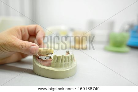 Dental technician working in dental laboratory, close up
