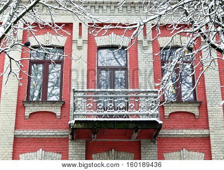 Facade of an old red brick building. Old vintage balcony covered with snow. Branches of a tree in the foreground.