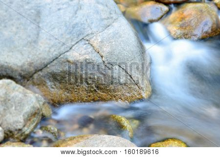 Blurred image of water flowing over rocks in dry evergreen forest,thailand.