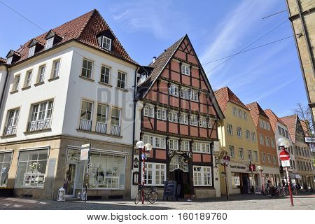 Osnabruck, Germany - April 22, 2016. Street view on Bierstrasse street in Osnabruck, with historic building Romantik Hotel Walhalla, commercial properties and people.