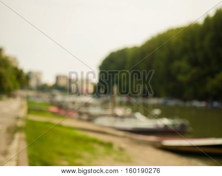 Blurred background of the river bank with boats on the shore and green trees on the opposite side of the river. Landscape of the river, boats and green trees, blurred background.