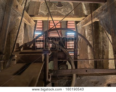 Picture of the rusty mechanism in the wooden belfry of the church. The wall of the belfry made of timber painted wih red colour. The sunlight shining feebly through the slit between red planks.