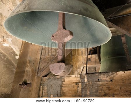 Picture of an old church bell in wooden belfry close up. Detail of an old green bell with red bell-tongue. Church bell hangs on the wooden timbers in the old belfry.