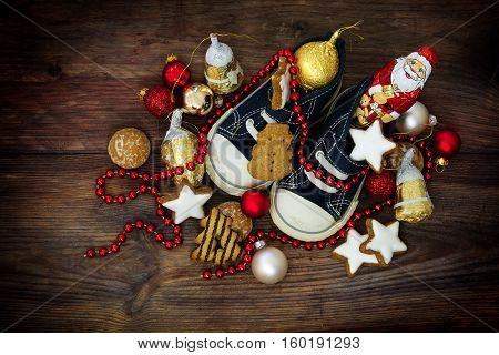 Childrens shoes filled with sweets cookies and red christmas decoration for Nicholas day on the 6th December in Germany on rustic wood view from above