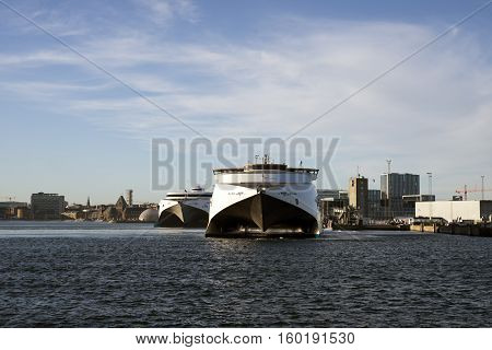 AARHUS DENMARK - NOVEMBER 24 2016: Two fast ferries KatExpress and Max Mols in Aarhus harbor and skyline in the background. November 24 2016
