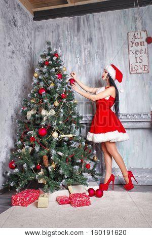 beautiful sexy girl wearing santa claus clothes . Young woman decorating Christmas tree with red balls at home