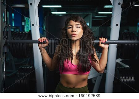 Woman workout with barbell in gym. Sexy girl with barbell in fitness club doing exercise