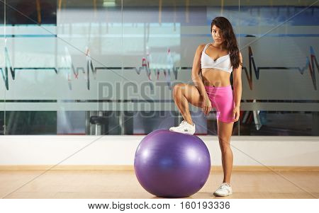 Finess club young woman trainer with ball in gym. Attractive girl stand on ball in fitness club