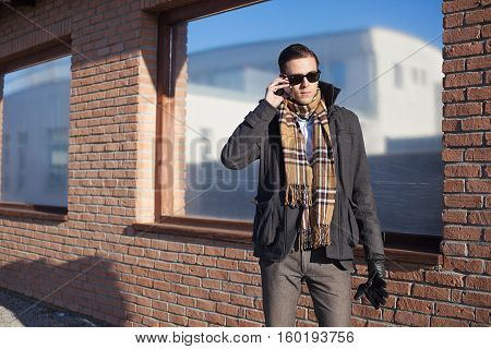 man in a winter jacket with serious face talking on a cellphone , standing outdoor next to the brick wall and reflective window, sunny day, winter