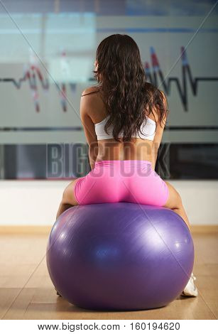 sexy hispanic woman sitting on fitness ball view from back. Slim girl sitting on ball