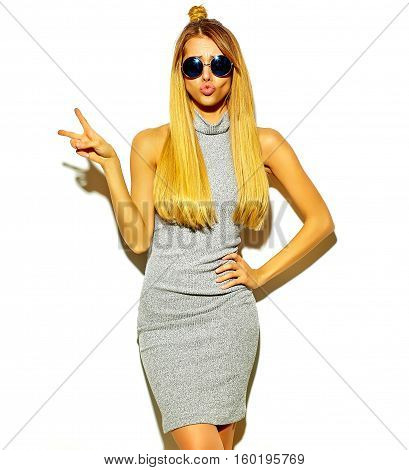 beautiful blond woman model in casual hipster gray summer clothes with no makeup isolated on white making a duck face and showing peace sign and making a duck face