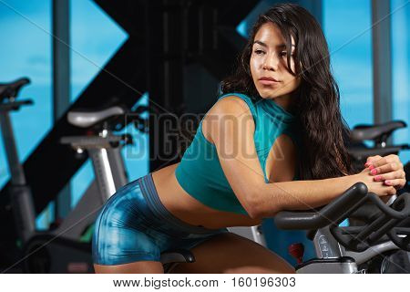 Young woman in fintess club bike doing exercises. Latina girl in gym