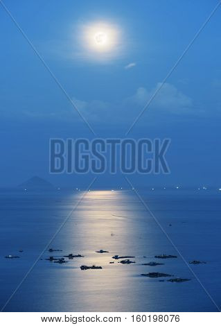 Full moon reflected in water of Nha Trang Bay of South China Sea in Vietnam at night. Marine farms illuminated by beautiful mysterious romantic moonlight. Island is visible in background.