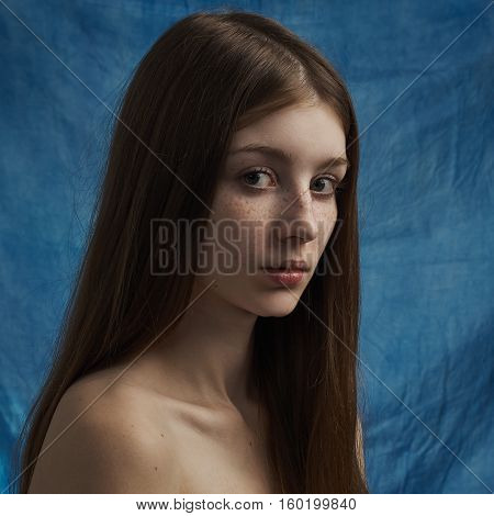 Beauty Theme: Portrait Of A Beautiful Young Girl With Freckles On Her Face And Wearing A Black Dress