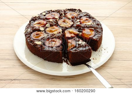 Closeup of a whole homemade Sticky Chocolate Plum Cake on a porcelain plate with one piece of cake on a cake server. Isolated on light brown wooden background.